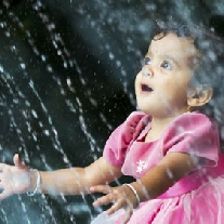 Young girl sitting in wonder with hands open and head up as rain comes down